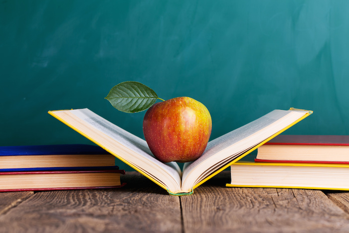 "Still life with school books and apple against blackboard with ""back to school"" on background"